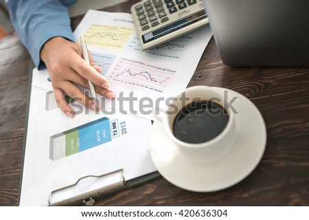 Front view of a businessman working in the office with a laptop and papers on his desk in his office as a consultant for the serious lawyer morning light, selected focus. - stock photo