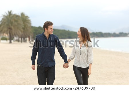 Front view of a couple in love taking a walk and looking each other on the beach in winter - stock photo