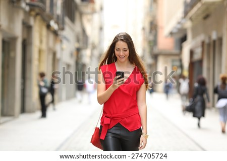 Front view of a fashion happy woman walking and using a smart phone on a city street - stock photo
