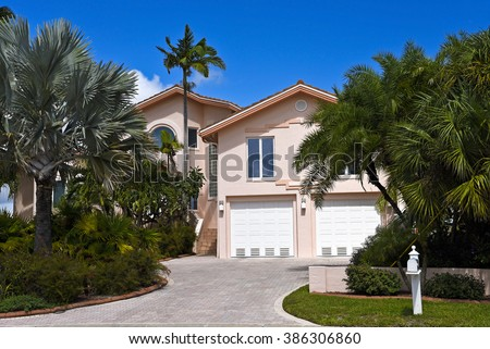 Front View of a Florida House with Beautiful Landscaping and Palm Trees  - stock photo