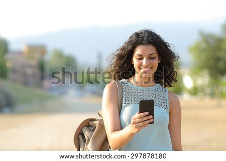 Front view of a happy girl walking and using a smart phone in a town - stock photo
