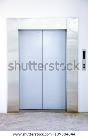 Front view of a modern elevator with closed doors in lobby - stock photo