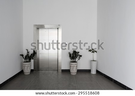 Front view of a office elevator with closed doors in lobby  - stock photo