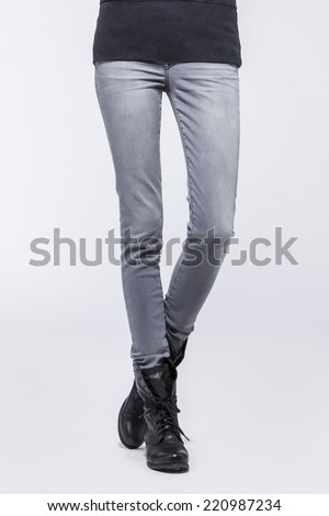 Front view of a standing woman(female) model wearing grey denim(trousers) with boots and black top isolated on a white background