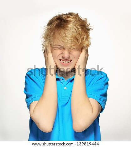 Front view of a teenage boy   with his hands covering ears. . - stock photo