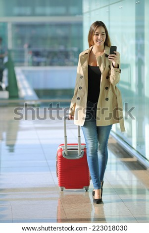 Front view of a traveler woman walking and using a smart phone in an airport corridor