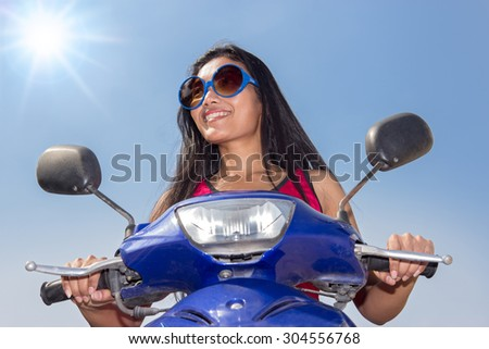 Front view of a woman sitting on a scooter on a blue background. Woman riding a motorcycle on a background of blue sky with shining sun. The sun shines on a woman driving a motorcycle - stock photo