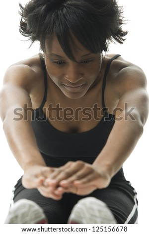 Front view of a young african american woman stretching - stock photo