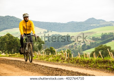 Front View of a Young Man With Bicycle on unpaved beautiful road in Brazil. Healthy Lifestyle Concept. Copyspace. - stock photo