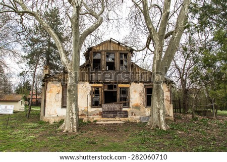 Front view of abandoned old building with dead trees. - stock photo