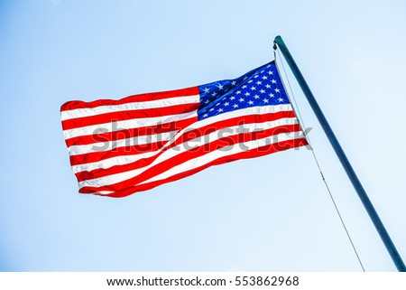 Front view of American flag on flagpole fluttering in wind on sky background.