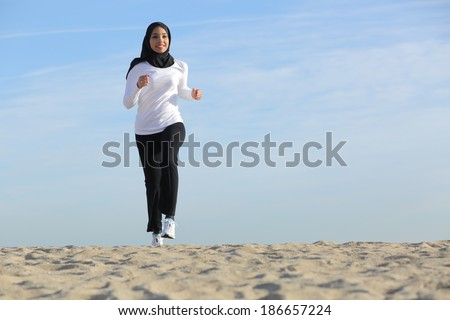 Front view of an arab saudi emirates woman running on the beach with the horizon in the background               - stock photo