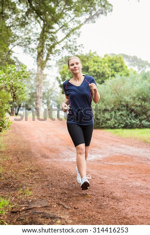 Front view of an athletic woman running on a footpath