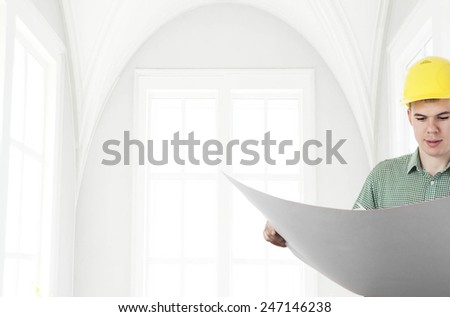 Front view of architect looking comparing blue print paper plan housing project with building wearing yellow helmet Back view businessman on wall and window background Empty copy space for inscription - stock photo