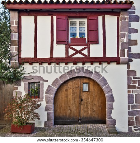 Front view of Basque traditional building in Saint-Jean-Pied-de-Port in French Basque country, Low Navarre, Atlantic Pyrenees, Aquitaine, France - stock photo