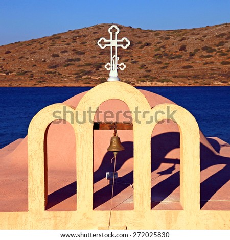 Front view of bell tower in a little classical orthodox Greek church and Mediterranean sea (Crete,Greece). - stock photo