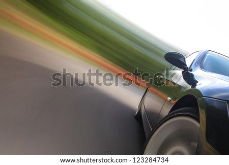 Front view of black car in turn with heavy blurred motion - stock photo