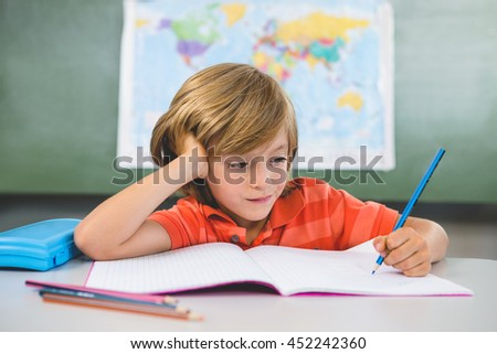 Front view of boy writing on book in classroom at school