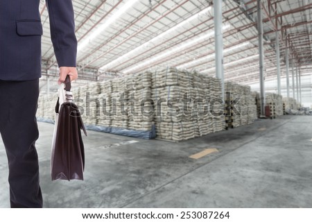 Front view of businessman with suitcase in warehouse - stock photo