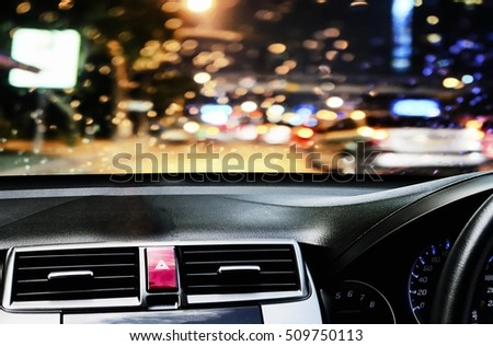 Front view of car looking out from inside with rain drop during twilight road background