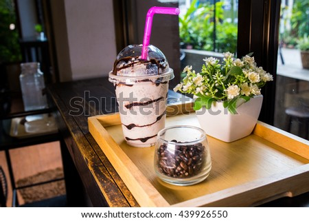front view of Chocolate milk shake with whipped cream served on the wooden tray in coffee bar - stock photo
