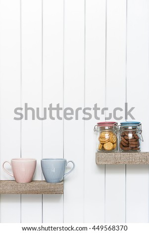 Front view of  coffee cup and cookies over white wall background on wooden shelf.
