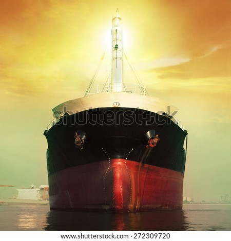 front view of commercial ship floating in port against sun light over sky - stock photo