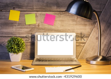 Front view of creative hipster desktop with blank white laptop screen, illuminated table lamp, smartphone, plant, colorful stickers and other stationery items. Mock up - stock photo
