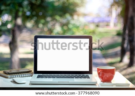 Front view of cup and laptop on table in Office park. - stock photo