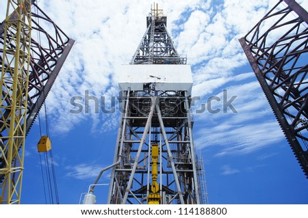 Front View of Derrick of Offshore Oil Drilling Rig and Rig Legs on Sunny Day - stock photo