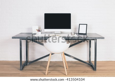 Front view of designer desk with blank computer monitor, frames and other items with white chair next to it. Wooden floor and white brick wall background. Mock up - stock photo