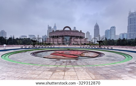 front view of famous historical chinese museum in Shanghai at sunrise with nobody around people square surrounded by modern high-rises - stock photo