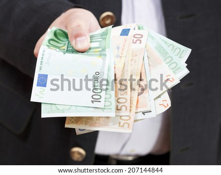 front view of fanned euro banknotes in male hands isolated on white background