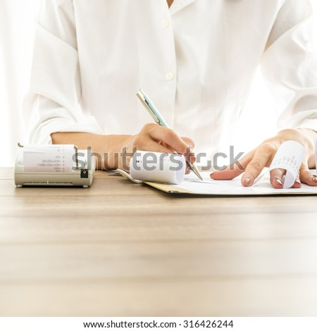 Front view of female bank employee in elegant white blouse writing something on receipts with documents and adding machine on her wooden desk. - stock photo