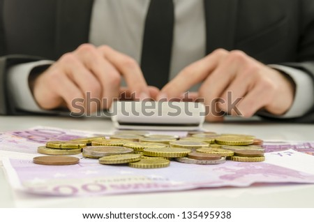 Front view of financial adviser working. With Euro banknotes and coins on his desk. Focus on money. - stock photo