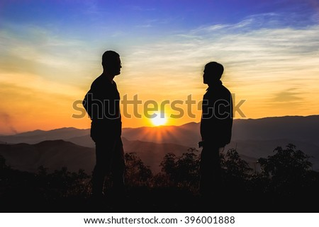 Front view of full body of two men silhouettes, who are looking each other on the mountain with beautiful sky and sunrise