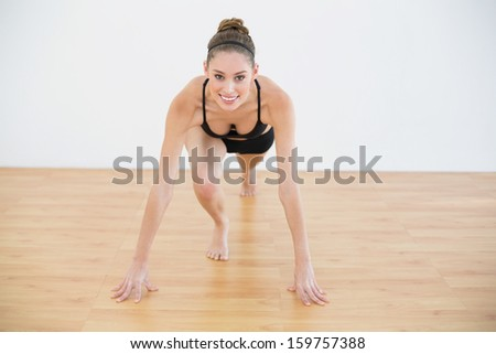 Front view of gleeful woman stretching her leg smiling at camera in sports hall