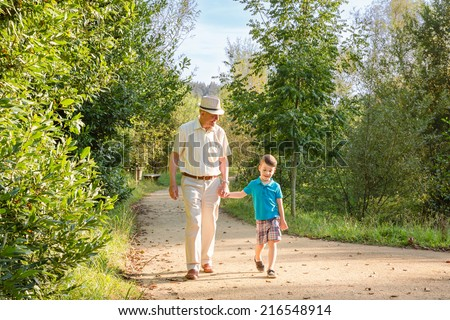 Front view of grandfather with hat and grandchild walking on a nature path - stock photo