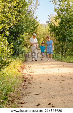 Front view of grandparents and grandchild walking on a nature path - stock photo