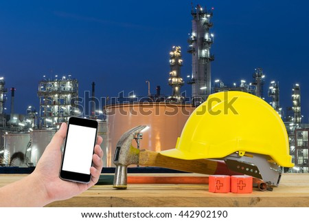 Front view of Hand holding the black smartphone and Yellow Safety Helmet, Hammer, Cutting tools on front of Oil refinery industry in night