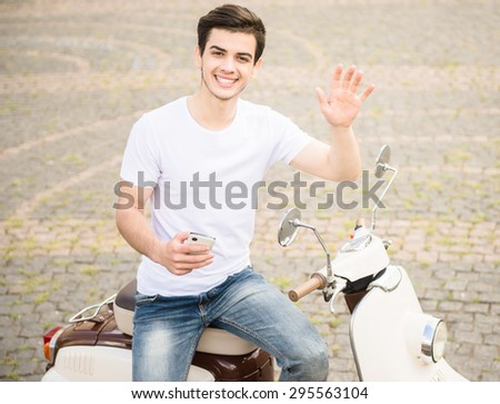 Front view of handsome man with phone sitting on scooter and posing to camera. - stock photo