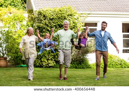 Front view of happy family playing in yard - stock photo