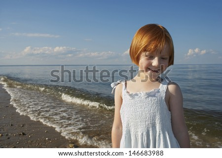 Front view of happy little girl standing at beach - stock photo