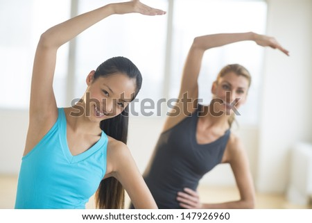 Front view of happy multi-ethnic women doing stretching exercise at gym - stock photo