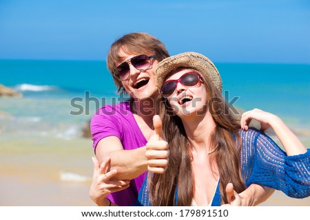 front view of happy young couple in sunglasses hugging on tropical beach