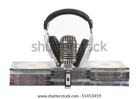 Front view of headphones, vintage microphone, cd, dvd stack - stock photo