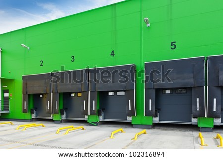 Front view of loading docks in the industrial warehouse with green wall and enumerated black doors - stock photo