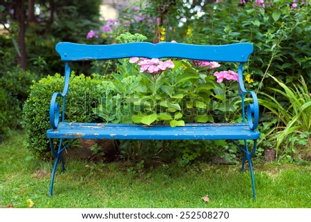 Front View of Lonely Old Blue Bench at the Garden with Beautiful Flowers at the Back. - stock photo