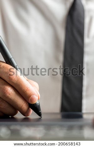 Front view of male graphic designer working on his digital tablet using digital pen to complete his work.