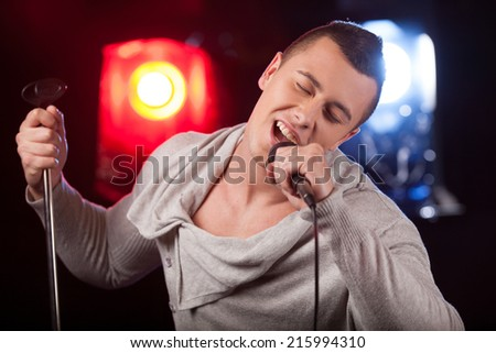 front view of male singer holding stand. handsome man singing into microphone alone - stock photo